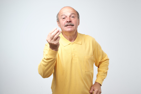 Photo pour Portrait of mature handsome man in yellow shirt showing italian gesture that means what do you want over white background. Bald gloomy guy do not have clue of what happening - image libre de droit