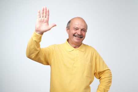 Photo for Friendly-looking attractive european pensioner in yellow t-shirt waives hand in hello gesture while smiling cheerfully. Grandfather welcoming his grandson. I am so glad to see you. - Royalty Free Image