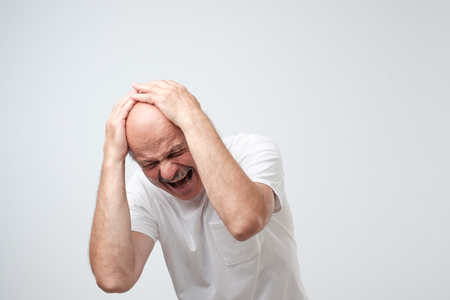 Foto de portrait mature hispanic desperate man holding his head in pain standing near a wall - Imagen libre de derechos