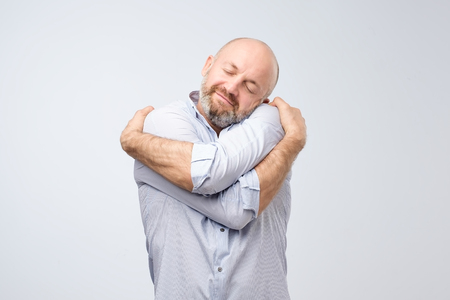 Foto de Closeup portrait of confident smiling man holding hugging himself isolated on grey wall background. Positive human emotion, facial expression. Love yourself concept - Imagen libre de derechos