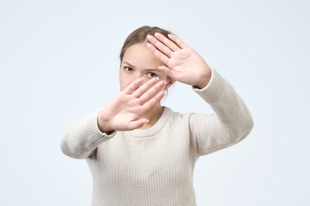 Foto de Serious pretty woman making stop hand sign palm gesture, isolated over white background. Stay away and do not touch me concept - Imagen libre de derechos
