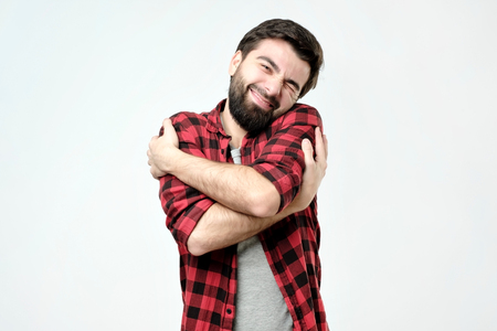 Foto de ortrait confident smiling man hugging himself. I am the best concept. Soft clothes after washing - Imagen libre de derechos