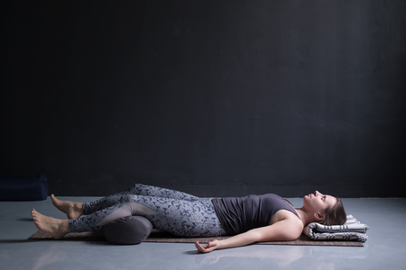 Photo pour woman working out, doing yoga exercise on wooden floor, lying in Shavasana - image libre de droit