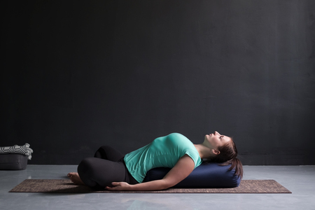 Photo pour Woman practicing yoga concept, lying in Reclined Butterfly exercise - image libre de droit