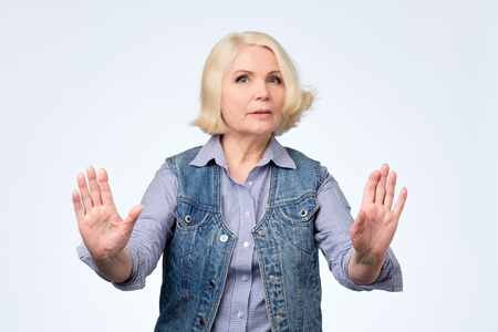 Foto de Serious senior european woman standing with outstretched hand showing stop gesture isolated over white background - Imagen libre de derechos