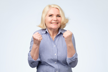 Foto de Cheerful granny with toothy smile raised hands and showing successful sign celebrate goal isolated on white background - Imagen libre de derechos