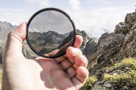 Foto de Hand puts a polarization filter to the camera, in the background a beautiful landscape and mountains - Imagen libre de derechos