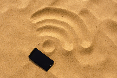Foto de mobile phone lying on the beach, in the sand, which drafted the WiFi sign - Imagen libre de derechos