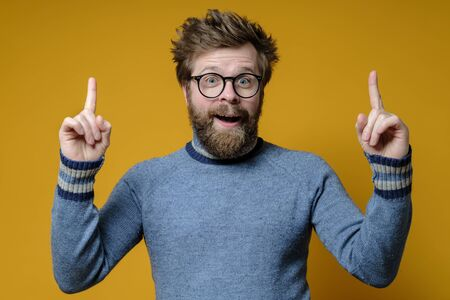 Photo pour Great idea. Shaggy, bearded man with glasses and a blue sweater raises index fingers up and looks joyfully with mouth open. - image libre de droit