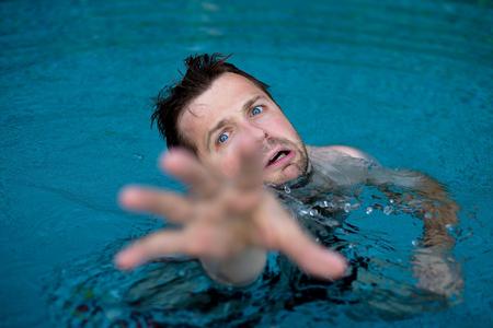 Foto de Drowning caucasian man in swimming pool asking for help. He stretching his hands in fear. - Imagen libre de derechos