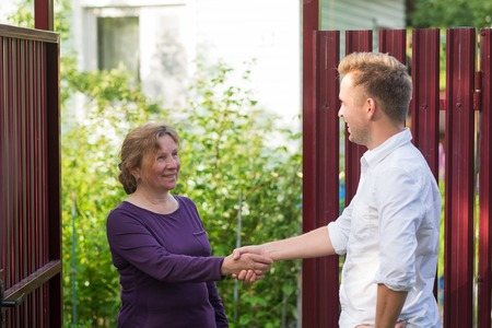 Photo for Neighbors discuss the news, standing at the fence. An elderly woman talking with a young man - Royalty Free Image