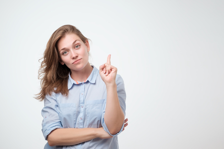 Foto de Beautiful smiling dreaming woman pointing with index finger up. Isolated over white background. Pay attention to this important information. Do not miss great sales concept - Imagen libre de derechos