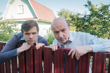 Photo pour two angry caucasian men carefully watching over the fence. Concept of curious neighbors and private life - image libre de droit