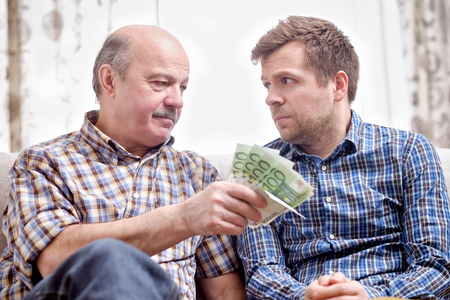 Photo pour Elderly father lends money to his adult son. He helps his child deal with financial problems. - image libre de droit