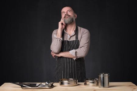 Foto de Bearded male chef showing different spices he uses. Secret of delicious food. Food, cooking, preparation concept. Professional food preparation concept. - Imagen libre de derechos