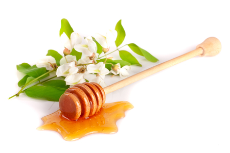 Foto de Honey stick with flowing honey and flowers of acacia isolated on white background - Imagen libre de derechos