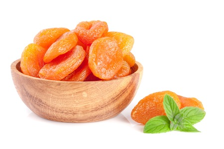 Photo for Dried apricots in a wooden bowl with mint leaves isolated on white background - Royalty Free Image