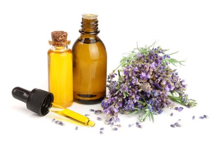 Foto de Bottle with aroma oil and lavender flowers isolated on white background - Imagen libre de derechos