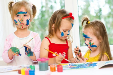 Photo pour three little girls drawing with gouaches on paper - image libre de droit