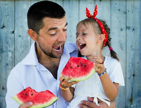 Foto de happy father playing with cute little daughter holding  watermelon - Imagen libre de derechos