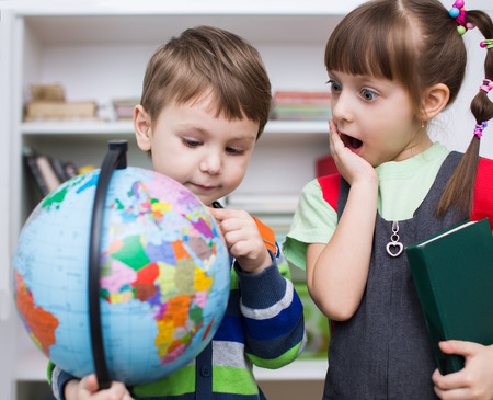 Photo pour Little kids are examining globe in the classroom - image libre de droit