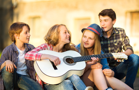 Photo for Portrait of happy teens playing the guitar surrounded by  friends - Royalty Free Image