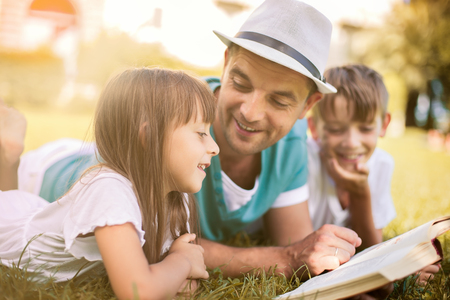 Photo pour Father reading a book to his children while laying outdoor on the grass in the park - image libre de droit