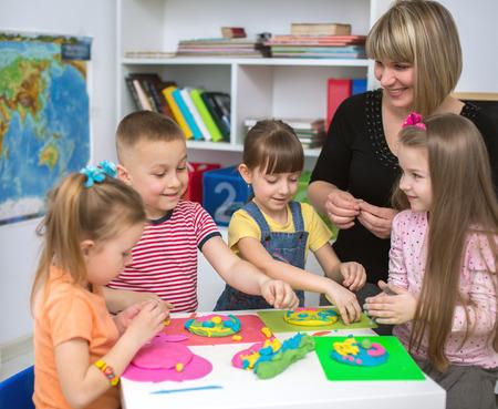 Photo pour Happy children with teacher  playing with color play dough at classroom - image libre de droit