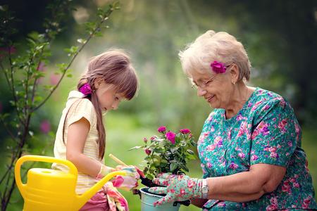 Foto de Happy Grandmother with her granddaughter working in the garden - Imagen libre de derechos