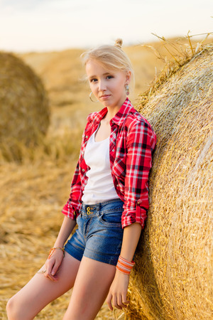Photo for Young girl on straw sheaves in a field. Girl on a wheat field in the rays of the setting sun. - Royalty Free Image