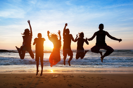 Foto de Six people with a shadow cast on them are jumping on beach at sunset. - Imagen libre de derechos