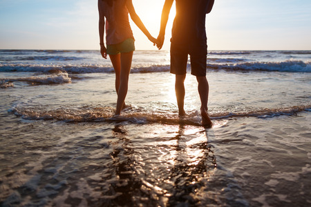 Photo for Young couple walking on the beach at sunset - Royalty Free Image