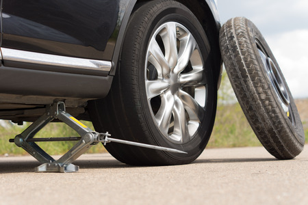 Foto de Jacking up a car to change a tyre after a roadside puncture with the hydraulic jack inserted under the bodywork raising the vehicle and the spare wheel balanced on the side - Imagen libre de derechos