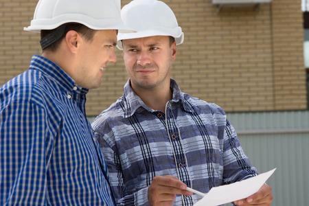 Foto de Middle Age Male Engineer and Foreman Discussing the House Project at the Construction Site. - Imagen libre de derechos