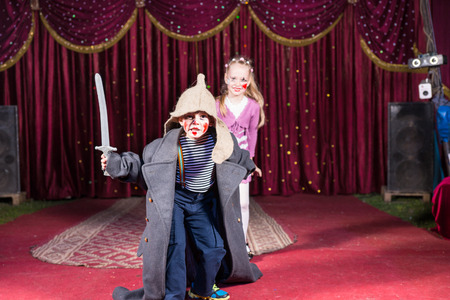 Foto de Cute talented boy playing the role of a brave Russian warrior fighting with a sward to defense his beautiful wife, in a theatrical performance at school - Imagen libre de derechos