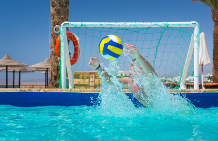 Photo pour Man trying to catch the ball in pool, playing water polo at the hotel on a sunny summer day - image libre de droit