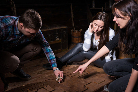Foto de Young people trying to solve a conundrum to get out of the trap, escape the room game concept - Imagen libre de derechos