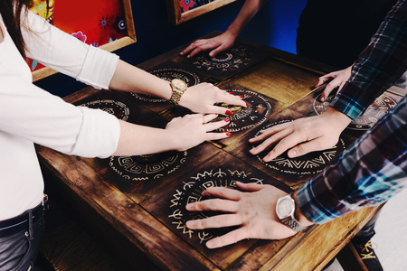Foto de The hands of young people move pieces of the Mexican style trying to get out of the trap, escape the room game concept - Imagen libre de derechos