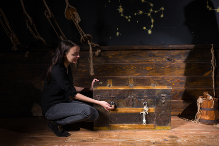 Foto de Young girl sits near a chest and trying to find a solution of conundrum to get out of the trap, escape the room game concept - Imagen libre de derechos