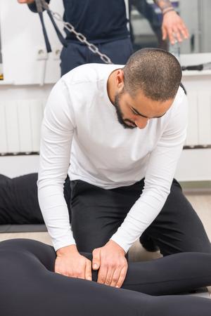 Foto de Handsome young black male masseur massaging woman's legs in gym - Imagen libre de derechos