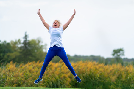 Foto de Older woman wearing workout outfit jumping for joy with arms and legs spread in midair in front of blurry yellow flowers - Imagen libre de derechos