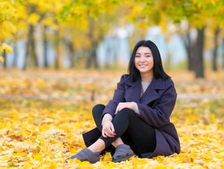 Foto de Attractive trendy young woman sitting amongst autumn leaves in a park smiling happily at the camera - Imagen libre de derechos