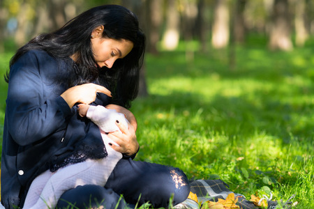 Photo pour A loving mother discreetly breastfeeding her baby in lush city park. - image libre de droit