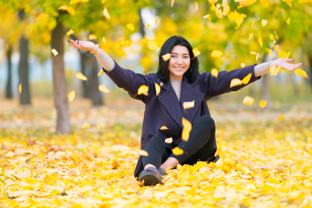 Foto de Happy young woman throwing autumn leaves in the air as she sits on the ground in a wooded park smiling at the camera - Imagen libre de derechos