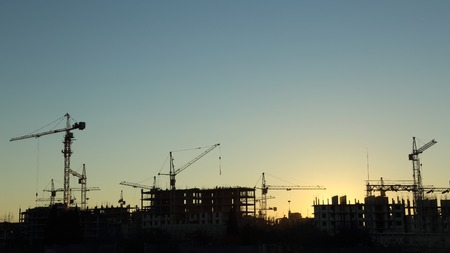 Photo pour silhouettes of construction  and power lines at sunset - image libre de droit