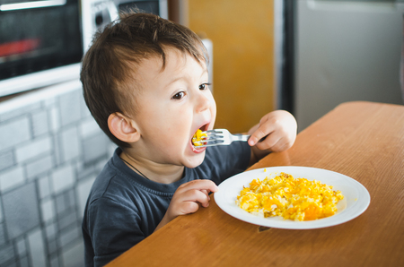 Photo for a child in a t-shirt in the kitchen eating an omelet, a fork - Royalty Free Image