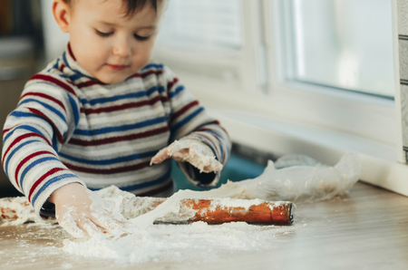 Photo for the child makes dough from flour house kitchen, played with the little chef - Royalty Free Image