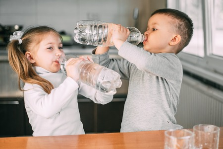 Photo pour Children girl and boy drink water from liter bottles very greedily, thirsty - image libre de droit