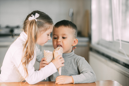 Foto de children, boy and girl eating ice cream cone in the kitchen are very fun to share with each other - Imagen libre de derechos