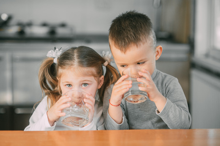 Photo pour Children boy and girl in the kitchen drinking water from glasses - image libre de droit